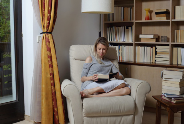 Young woman wearing cozy sweater,sitting in comfortable armchair, enjoying reading a book at home library